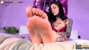 Barefoot tattoed redhead massaging her cute feet with oil