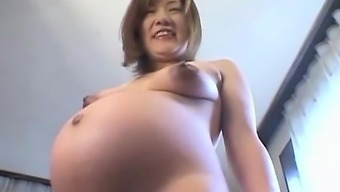 Asian preggo contributes with her tits